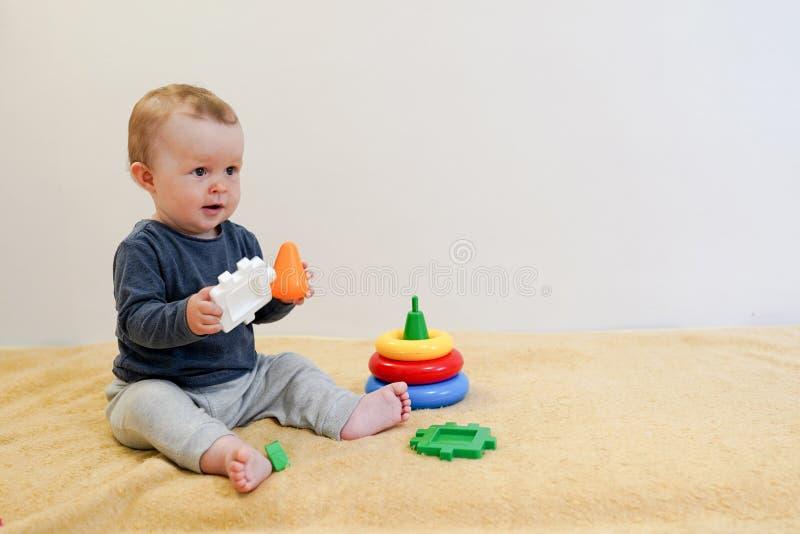 Baby die en met kleurrijk speelgoed thuis smilling spelen kindachtergrond met exemplaarruimte Vroege ontwikkeling voor kinderen stock afbeeldingen