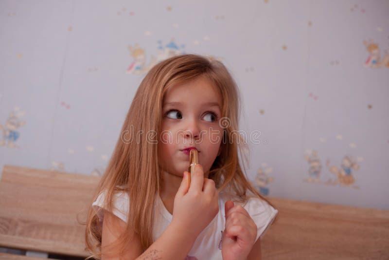 Baby die gilr lippenstift gebruiken stock foto