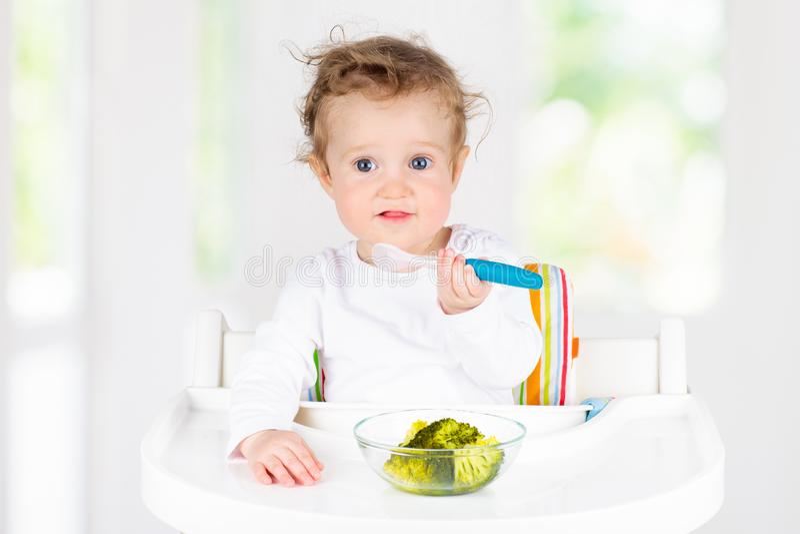 Baby die groenten eten Stevig voedsel voor zuigeling stock foto's