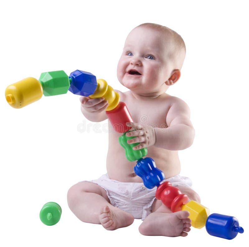Baby die grote plastic parels houdt. stock afbeeldingen