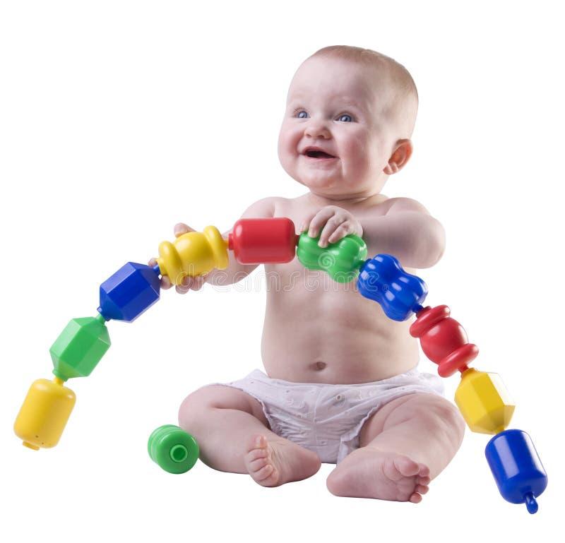 Baby die grote plastic parels steunt. stock fotografie