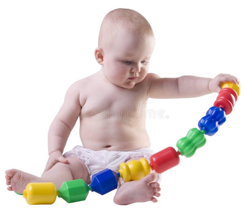 Baby die grote plastic parels uittrekt. stock afbeelding