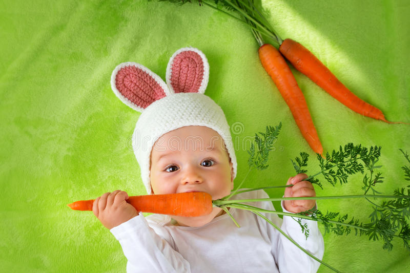 Baby die in konijnhoed wortel eten stock afbeelding