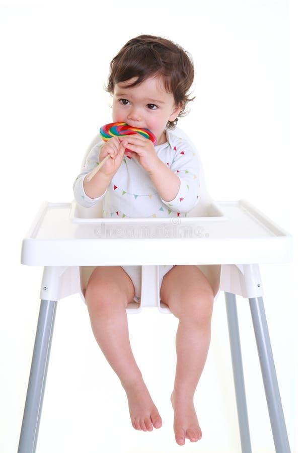 Baby die lollypop bijt stock foto