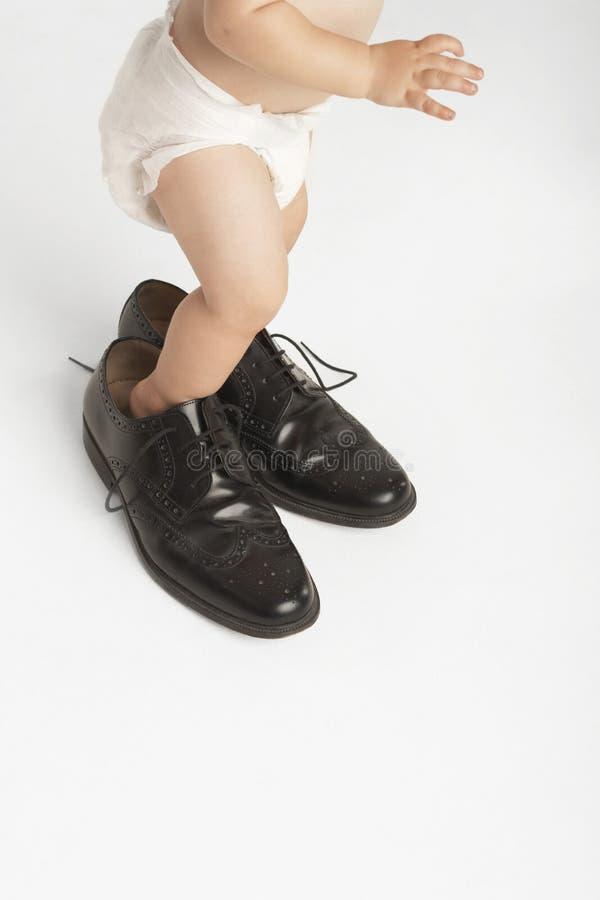 Baby die Man Schoenen dragen stock fotografie