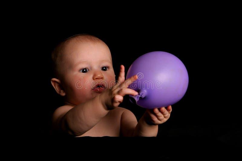 Baby die met ballon wordt geboeid royalty-vrije stock afbeelding