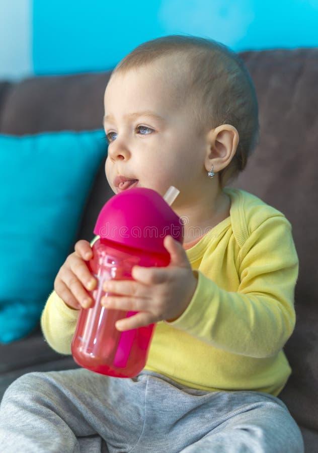 Baby die met blauwe ogen fles houden stock afbeeldingen