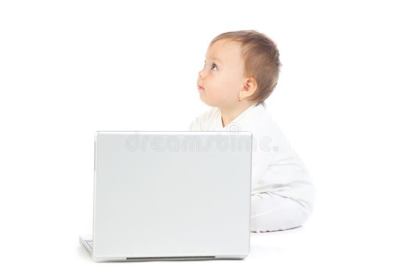 Baby die met laptop computer wordt gezeten stock afbeelding