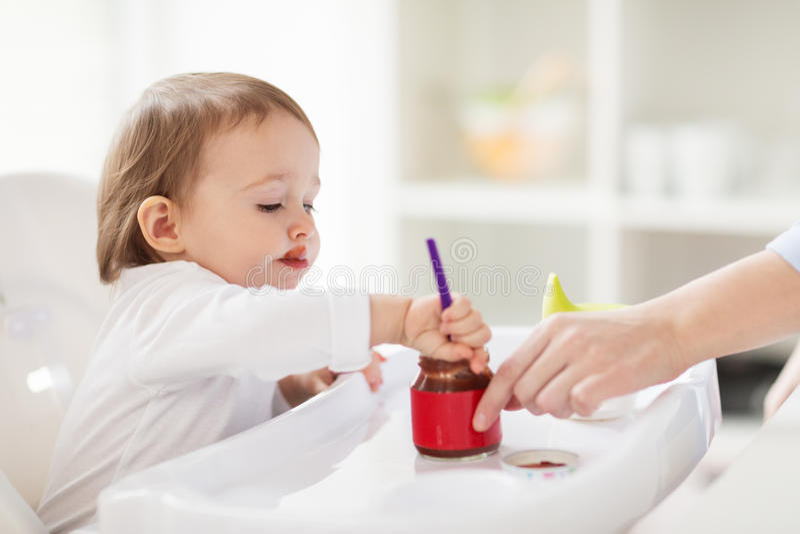Baby die met lepel puree van kruik thuis eten royalty-vrije stock fotografie
