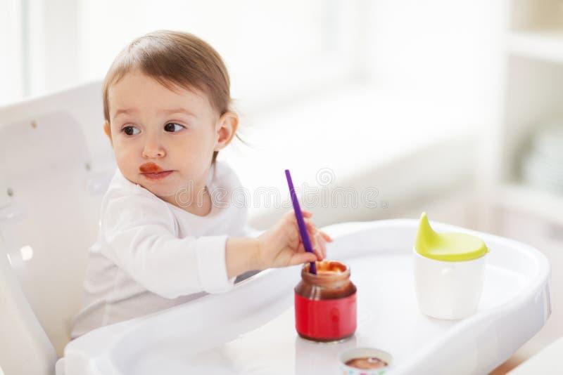Baby die met lepel puree van kruik thuis eten stock afbeelding