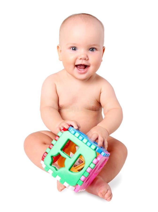 Baby die met stuk speelgoed in geïsoleerde handen glimlachen stock foto
