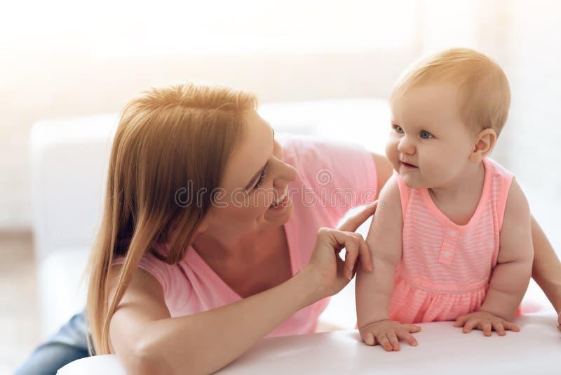 Baby die met vrolijke jonge glimlachende moeder koesteren royalty-vrije stock foto