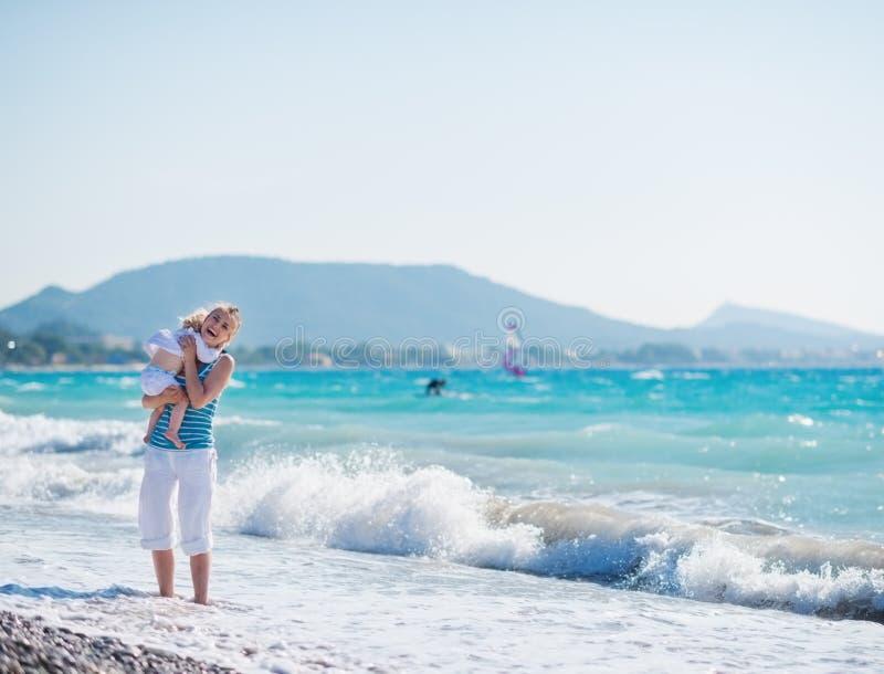 Baby die moeder bevindende op zee kust koestert royalty-vrije stock foto's