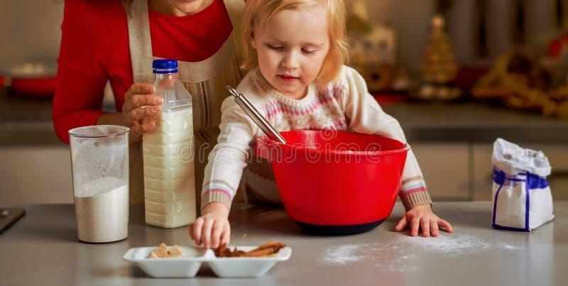 Baby die moeder helpen Kerstmiskoekjes in Kerstmis maken verfraaien royalty-vrije stock foto's
