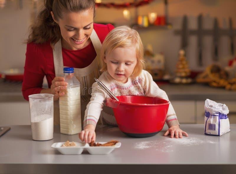 Baby die moeder helpen Kerstmiskoekjes in keuken maken stock foto