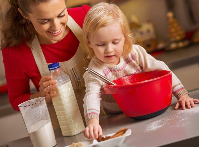 Baby die moeder helpen Kerstmiskoekjes in keuken maken royalty-vrije stock afbeelding