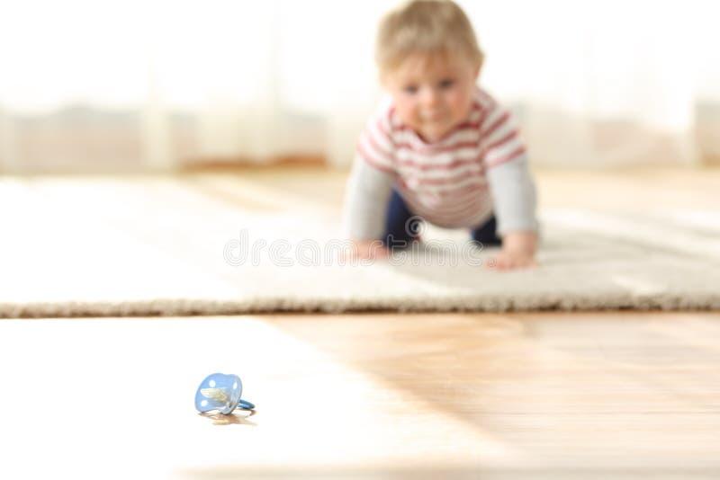 Baby die naar een vuile fopspeen op de vloer kruipen stock foto's