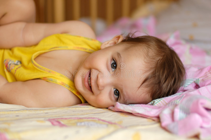 Baby die op bed ligt royalty-vrije stock foto