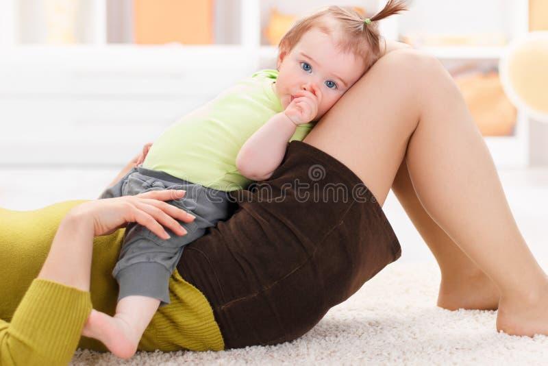 Baby die op haar moederbenen rusten stock afbeeldingen