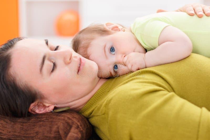Baby die op haar moederborst rusten stock foto's