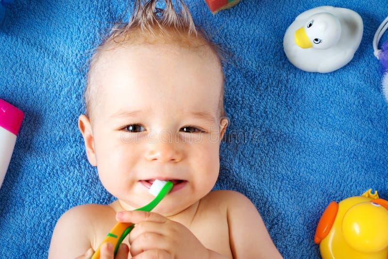 Baby die op handdoek met washulpmiddelen liggen royalty-vrije stock afbeelding