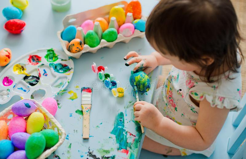 Baby die Paaseieren schilderen stock afbeeldingen