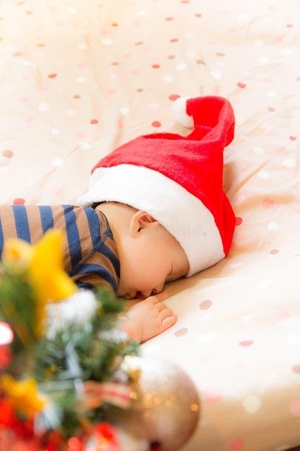 Baby die Santa Claus-hoedenslaap dragen door Kerstboom stock foto's