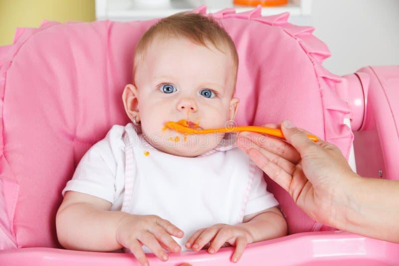 Baby die wortel eet stock foto