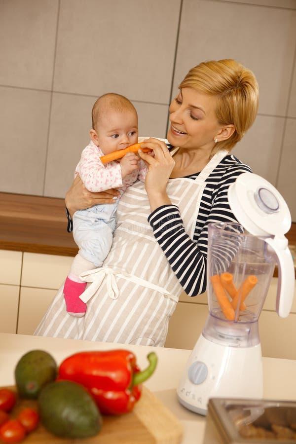 Baby die wortel met moeder eten royalty-vrije stock foto's