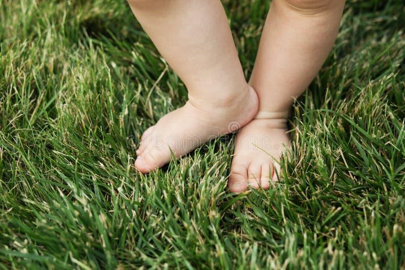 Baby die zich blootvoets op het gras bevinden stock foto's