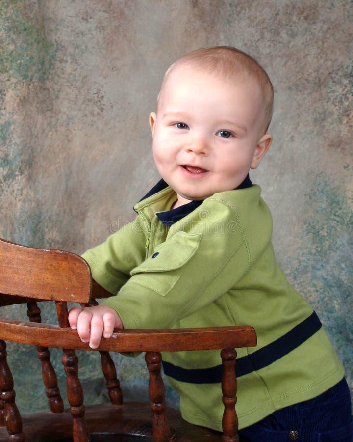 Baby die zich door Houten Stoel bevindt stock foto's