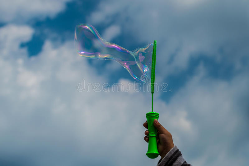 Baby doing soap bubbles - hand on sky, clouds background. Baby doing soap bubbles - hand on sky, clouds background stock image