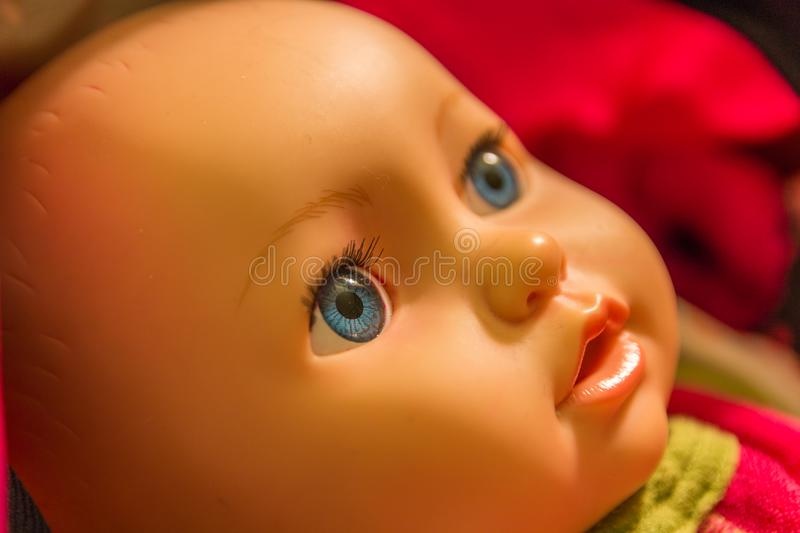 Baby doll with blue eye. Blue eyed baby doll starring closeup royalty free stock photography