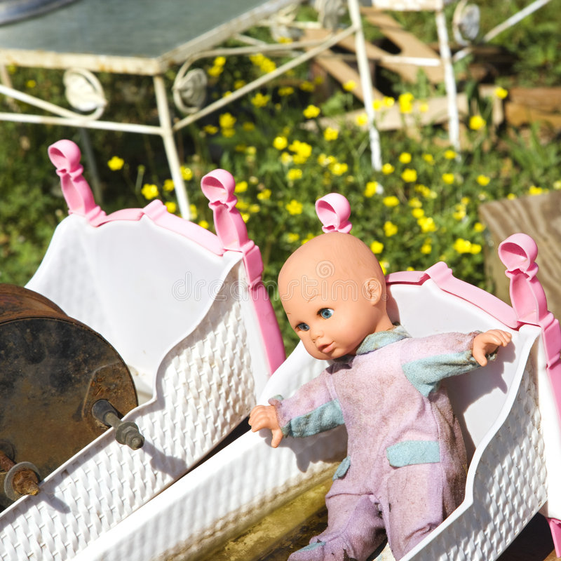 Baby doll in crib. Old discarded baby doll lying in crib in junkyard field stock photo