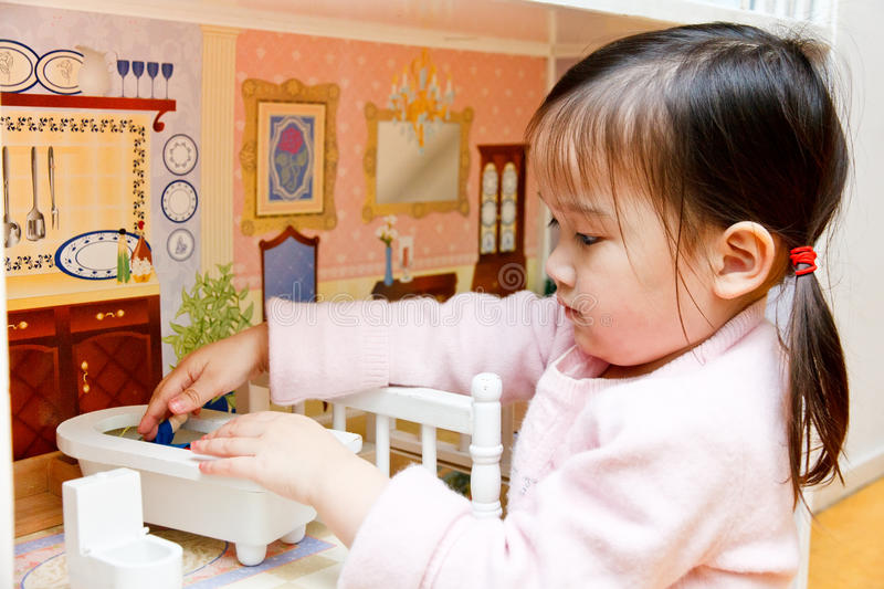 Baby Doll House. Little Asian Girl giving bath to her doll with baby doll house stock images