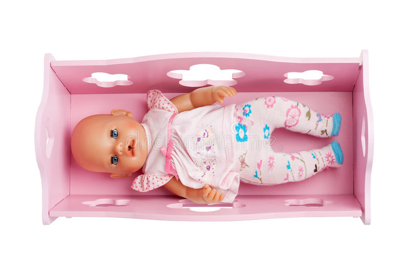 A baby doll laying in the pink crib royalty free stock photos