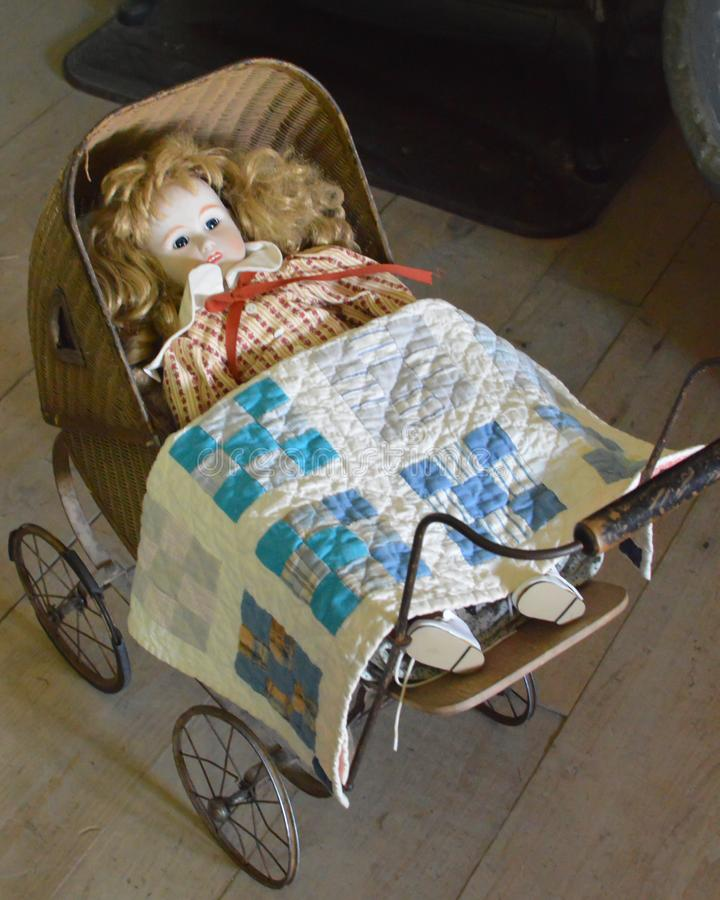 Baby Doll in Old Fashioned Carriage with Quilt royalty free stock photography