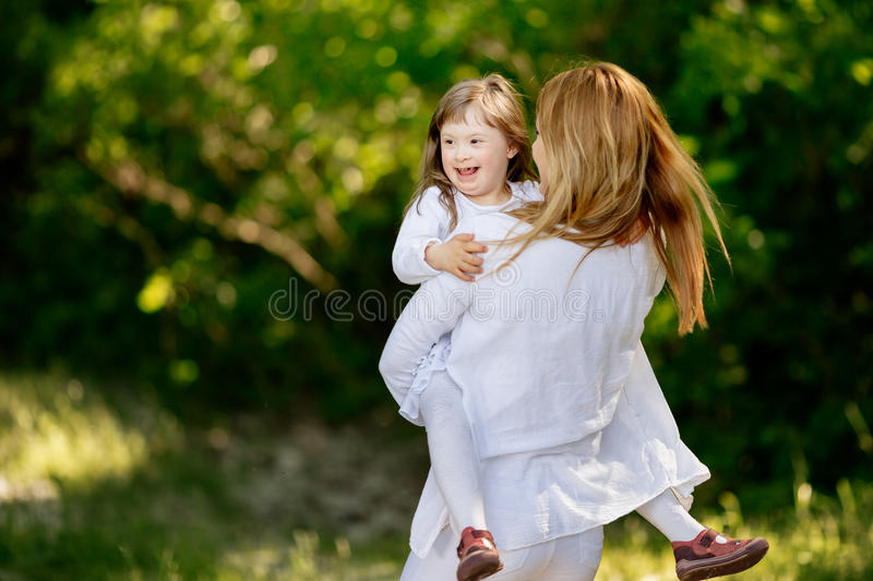 Baby with down sydrome enjoying outdoor play. With sister stock photography