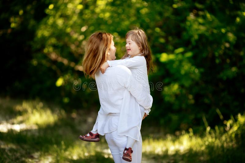 Baby with down sydrome enjoying outdoor play. With sister royalty free stock photography