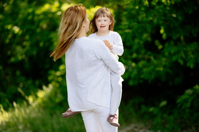Baby with down sydrome enjoying outdoor play. With sister stock images
