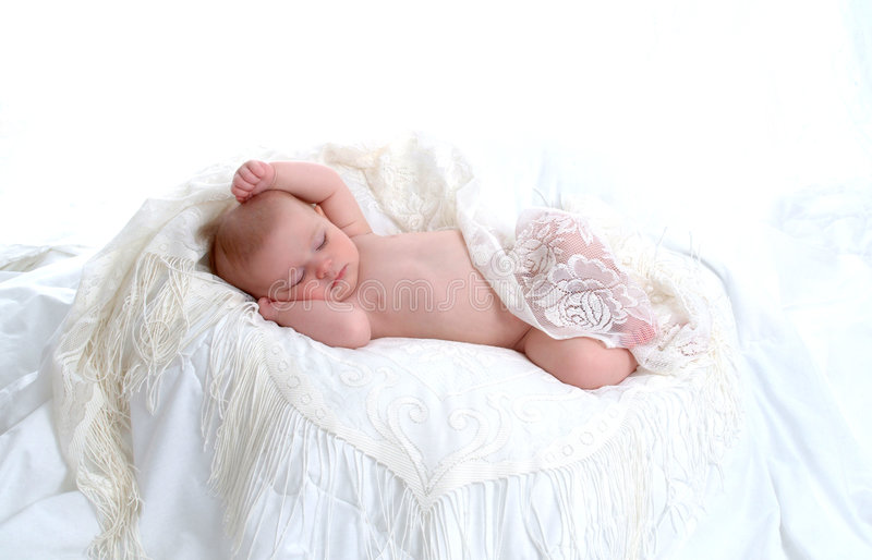 Baby Dreamer. Sleeping baby lying on white blanket with lace cover stock photos