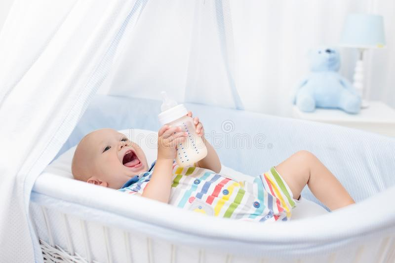Baby drinking milk. Boy with formula bottle in bed. Baby drinking milk in white crib. Infant boy with formula bottle in bed. Kids nutrition. Healthy food and stock photo