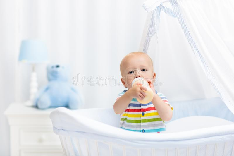 Baby drinking milk. Boy with formula bottle in bed. Baby drinking milk in white crib. Infant boy with formula bottle in bed. Kids nutrition. Healthy food and royalty free stock photography
