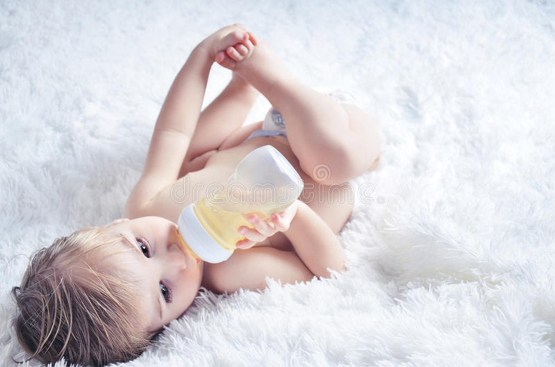 Baby drinks from bottle stock image