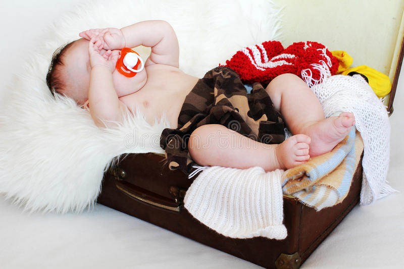 Baby with dummy lies in a suitcase with clothes. Baby with dummy age of 3 months lies in a suitcase with clothes royalty free stock photography