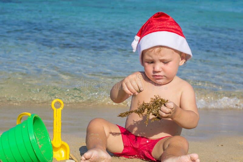 Baby durch das Meer in einer Kappe von Santa Claus lizenzfreies stockfoto