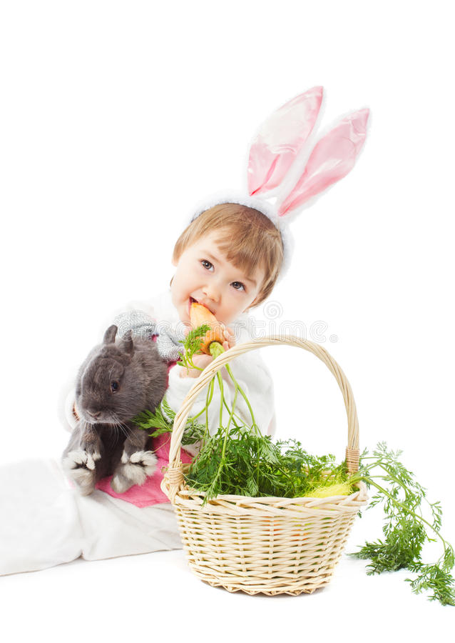 Baby in easter bunny costume eating carrot, kid girl rabbit hare. Baby in easter bunny costume eating fresh carrot, kid girl holding hare rabbit over white royalty free stock photography