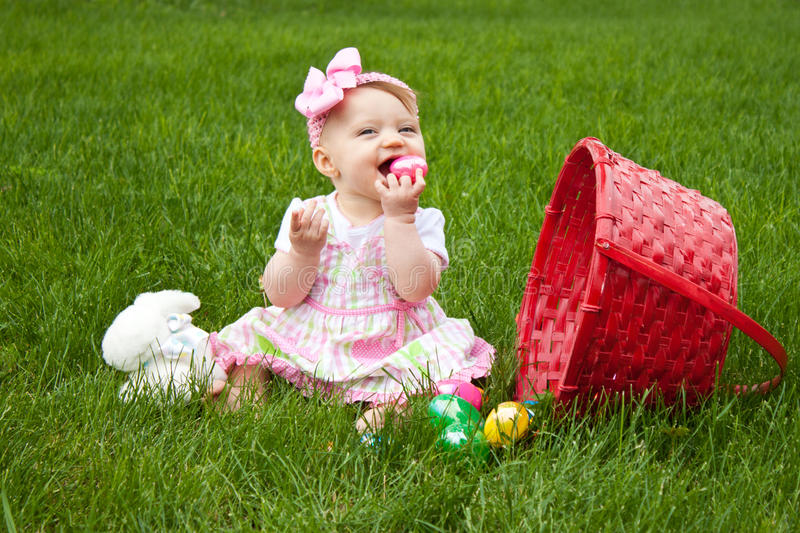 Baby Easter Eat Egg. Baby Smiling while holding an Easter egg beside a red basket royalty free stock photos