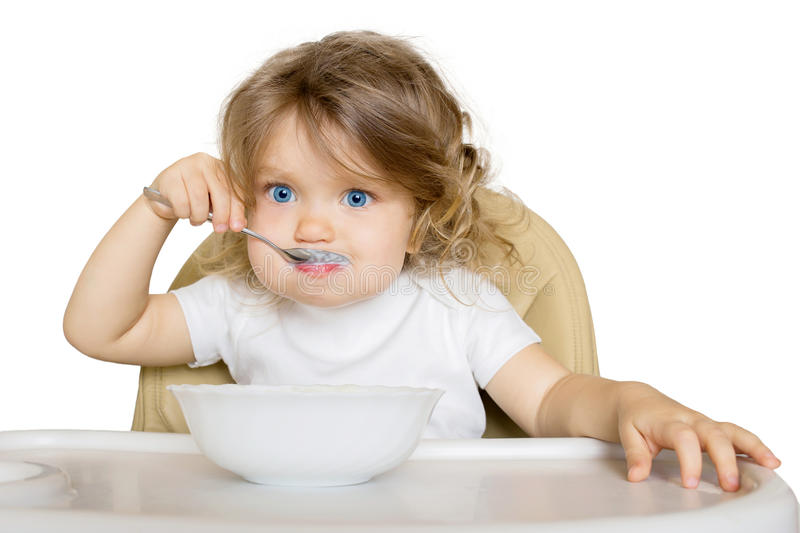 Baby eating baby food in high chair. stock image