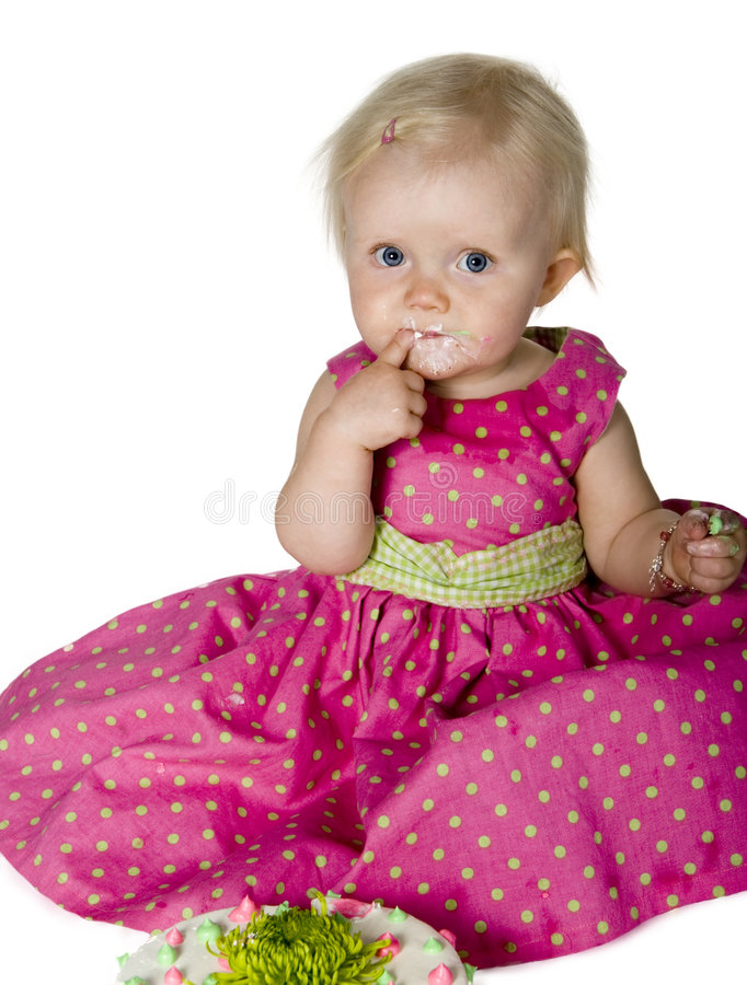 Baby eating cake. Baby girl with icing on her face royalty free stock photography